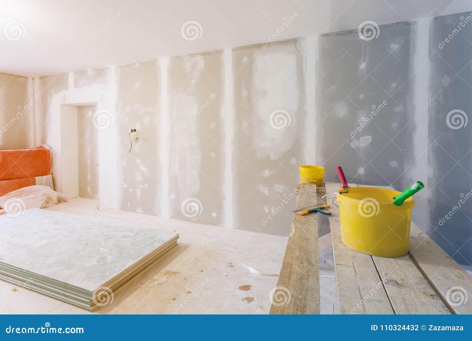 Нож замазки, желтые ведра с клеем и роликами клея на деревянной доске в комнате под конструкцией