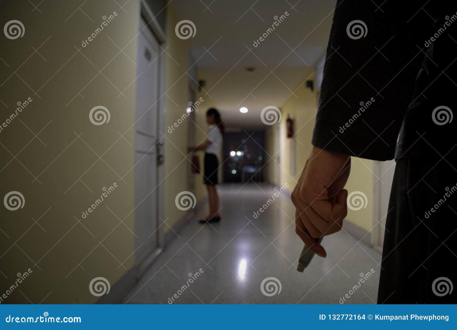Нож удерживания руки разбойника или похитителя смотря к бизнес-леди которая открывая дверь вечером, фокус на людях, уголовная кон