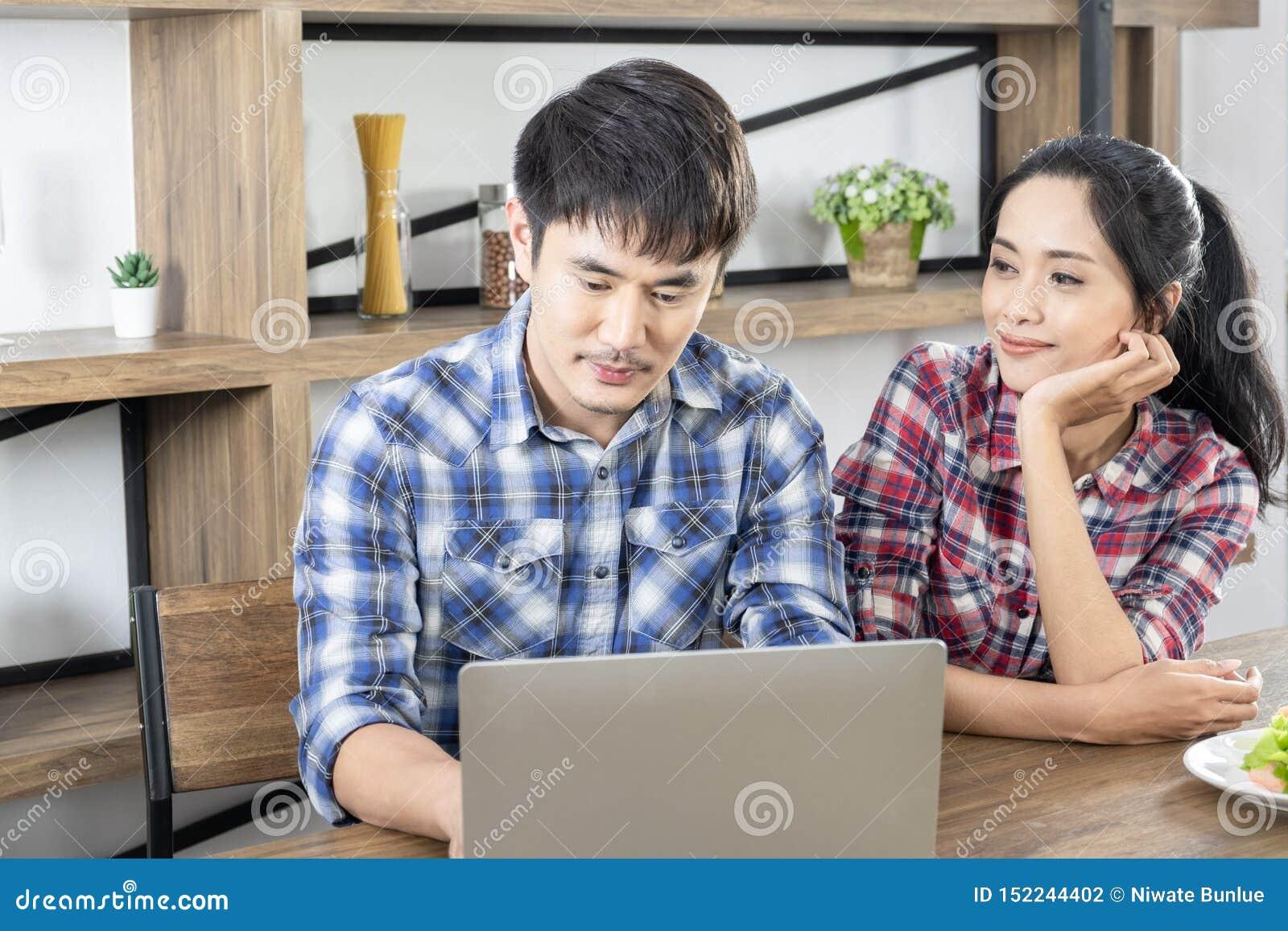 Ноутбук молодых азиатских прекрасных пар наблюдая для ходя по магазинам онлайн дома офиса