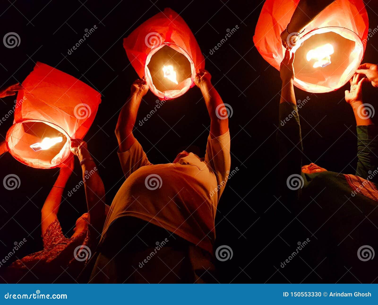 Ноябрь 2018, Kolkata, Индия Человек 3 выпуская освещенный бумажный горячий воздушный шар в фестивале фонарика неба вечером в Kolk