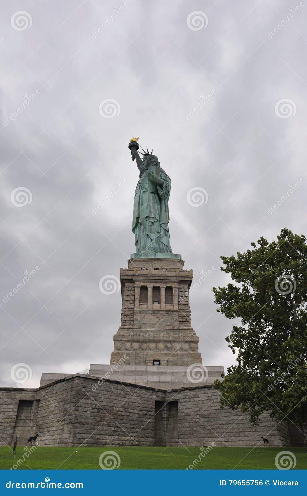 Нью-Йорк, 2-ое августа: Статуя свободы на драматическом небе в Нью-Йорке