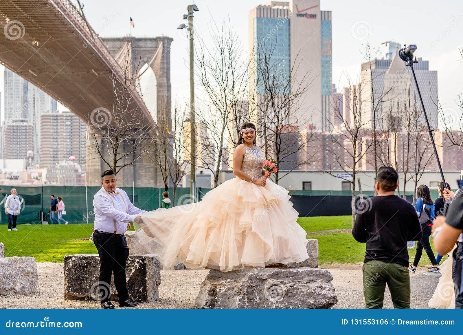 НЬЮ-ЙОРК, США - 28-ОЕ АПРЕЛЯ 2018: Невеста представляя во время фотосессии в Dumbo, Бруклине, Нью-Йорке