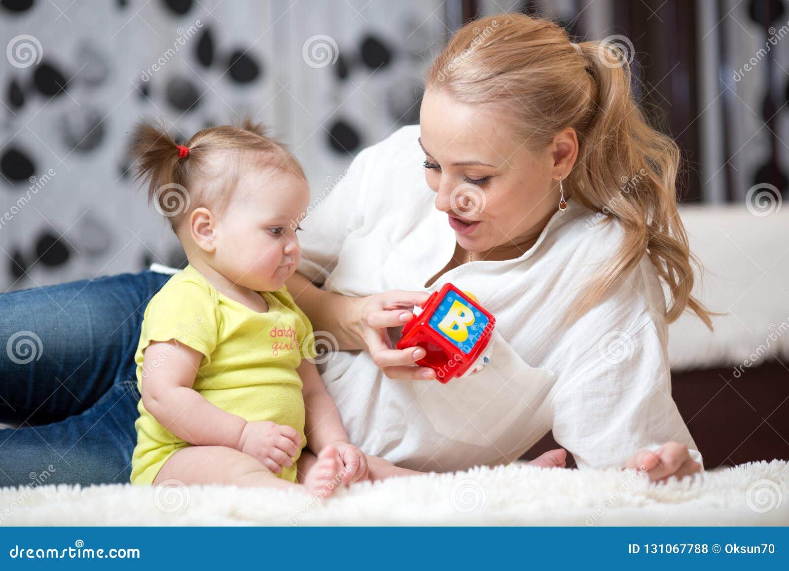 Няня и младенец играя с кубами игрушки дома