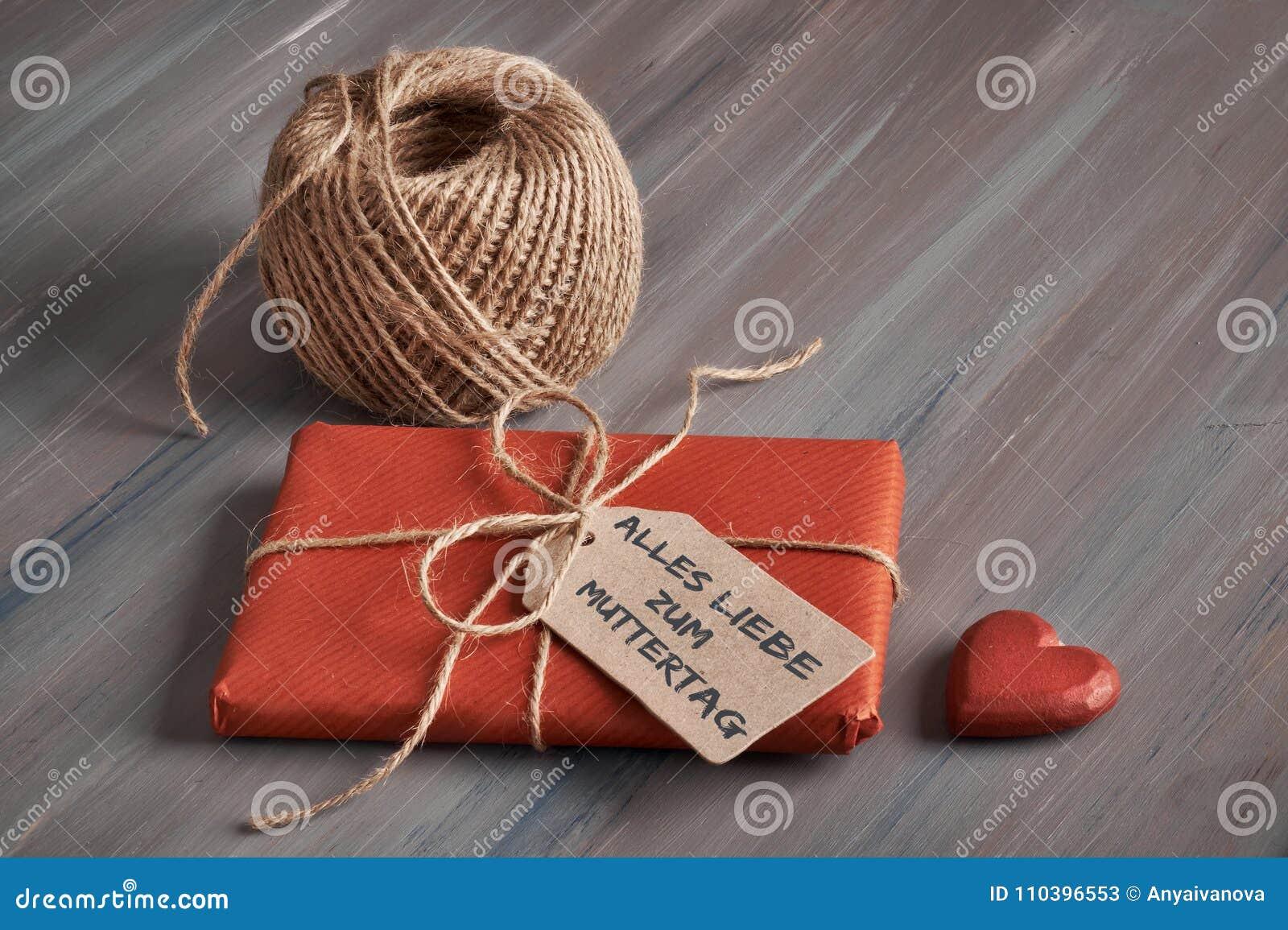 Обернутый подарок связанный вверх с шнуром, биркой картона с текстом