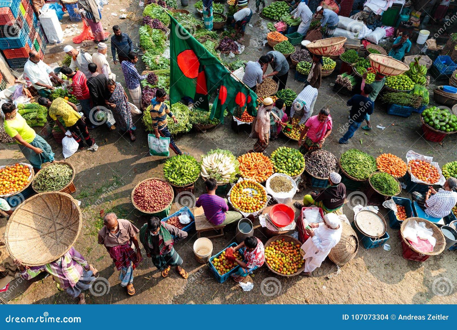 Обзор сцены улицы на местном vegetable рынке в Дакке, Бангладеше показывая плодоовощи colorfull и специи