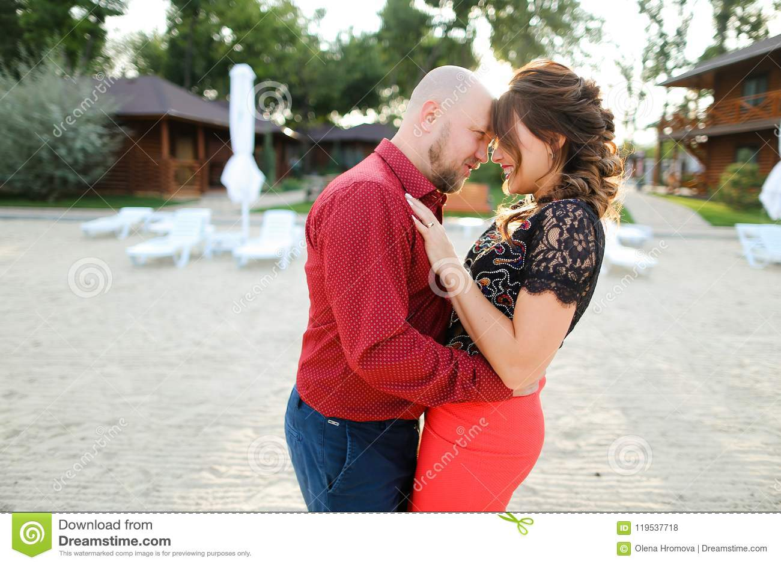 Облыселый кавказский супруг нося красную рубашку и танцуя с женой на задворк