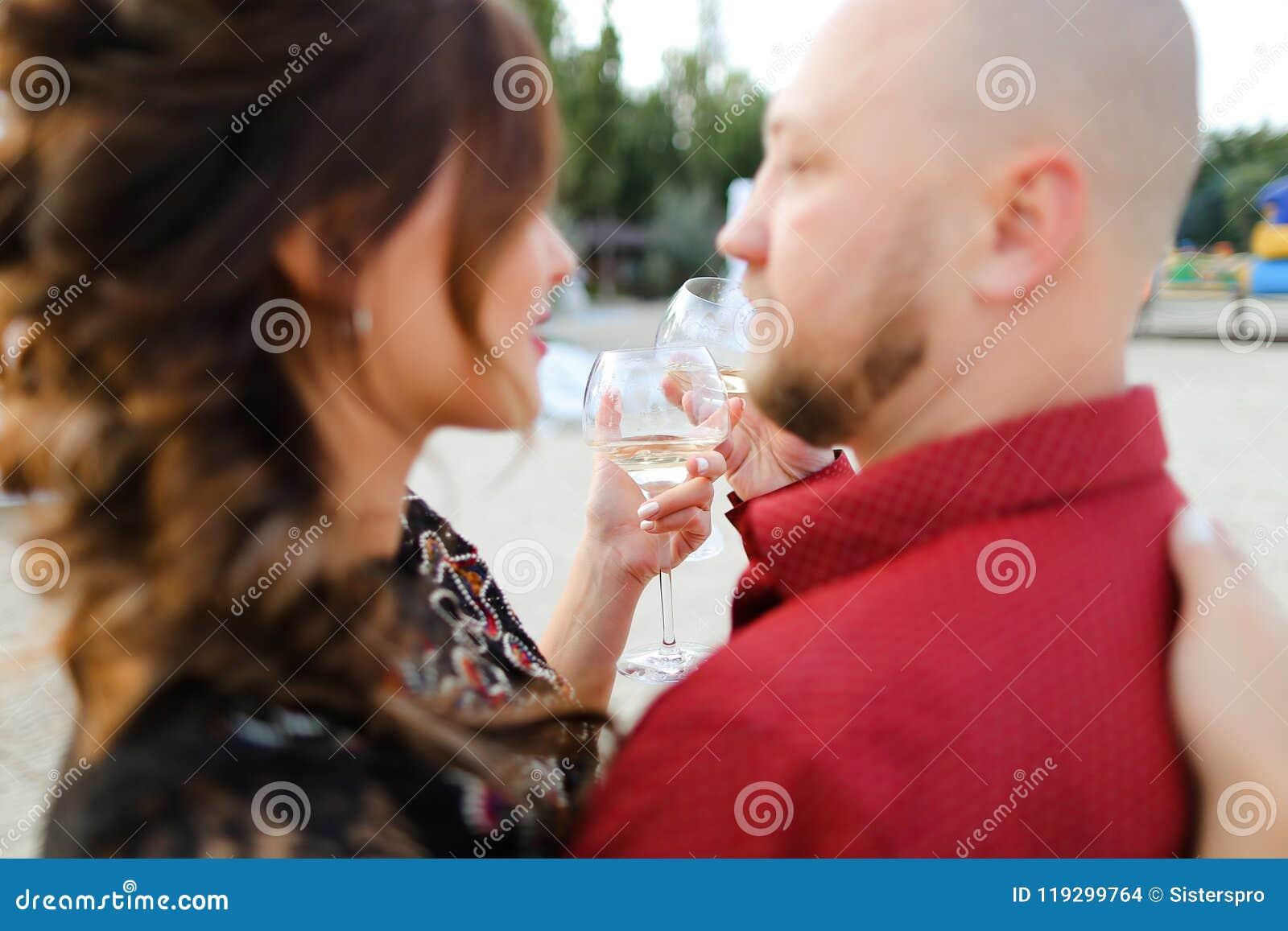 Облыселый супруг нося красные танцы рубашки с женой и выпивая вино