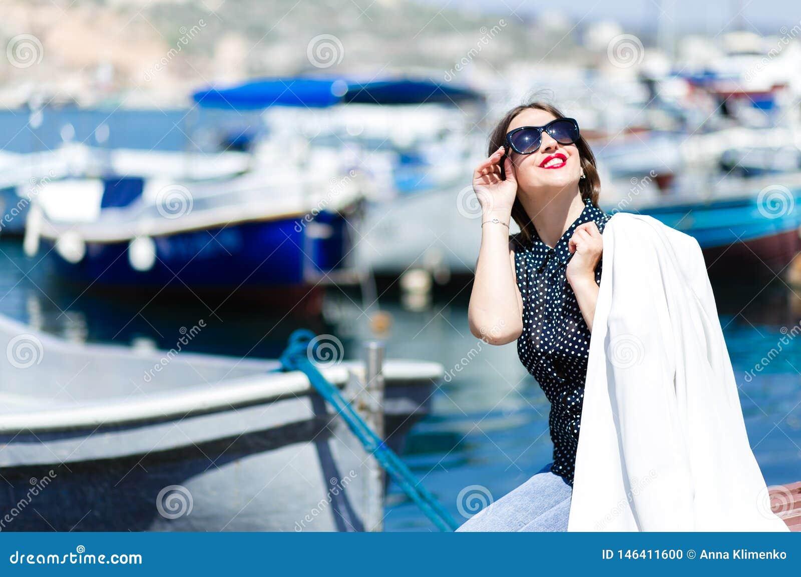 Обмундирование whilte моды ультрамодной красивой смеясь женщины в солнечных очках представляя на морской предпосылке шлюпок