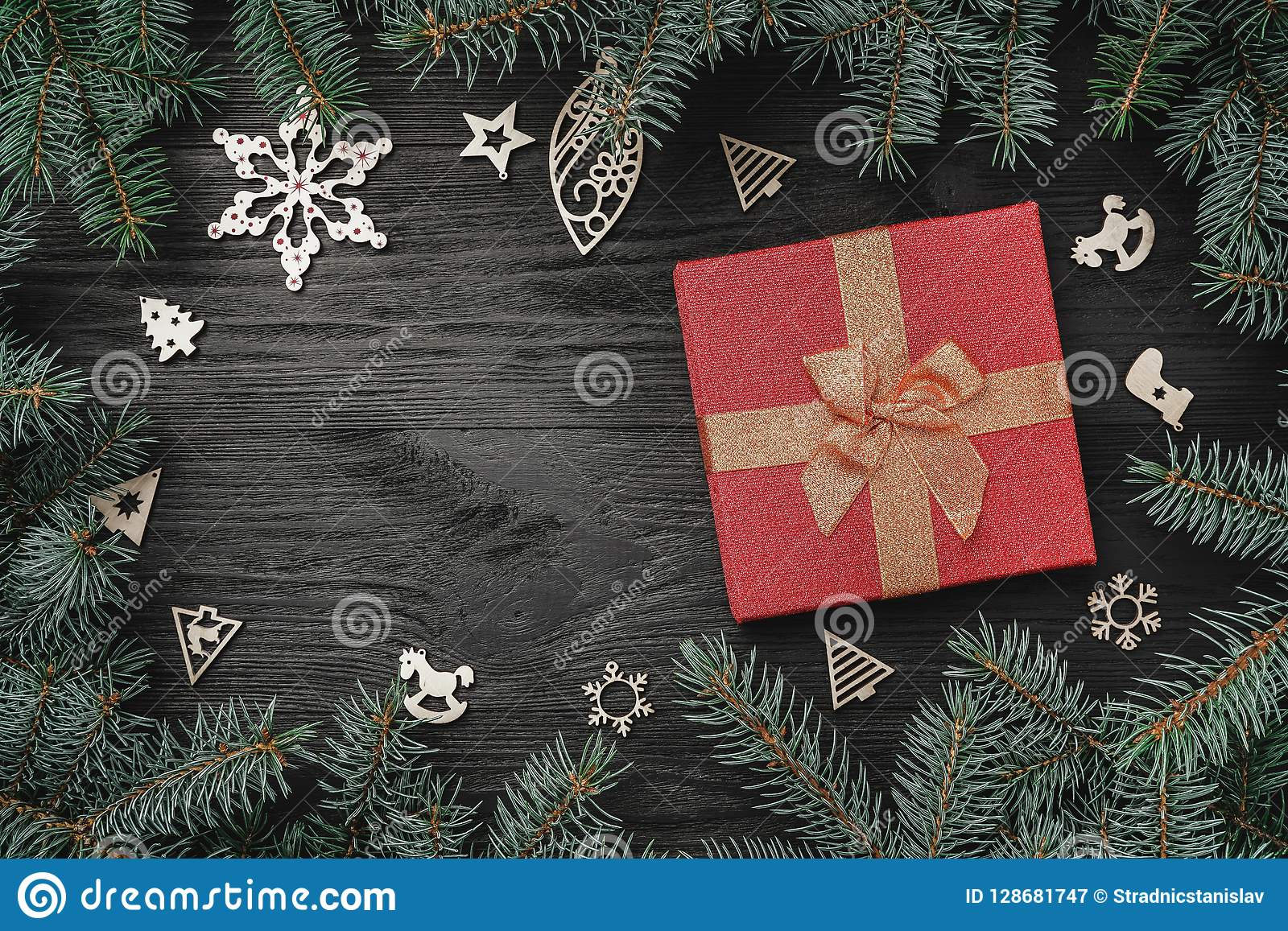 Обои зимних отдыхов на черной предпосылке Красный подарок и деревянные игрушки Ели вокруг