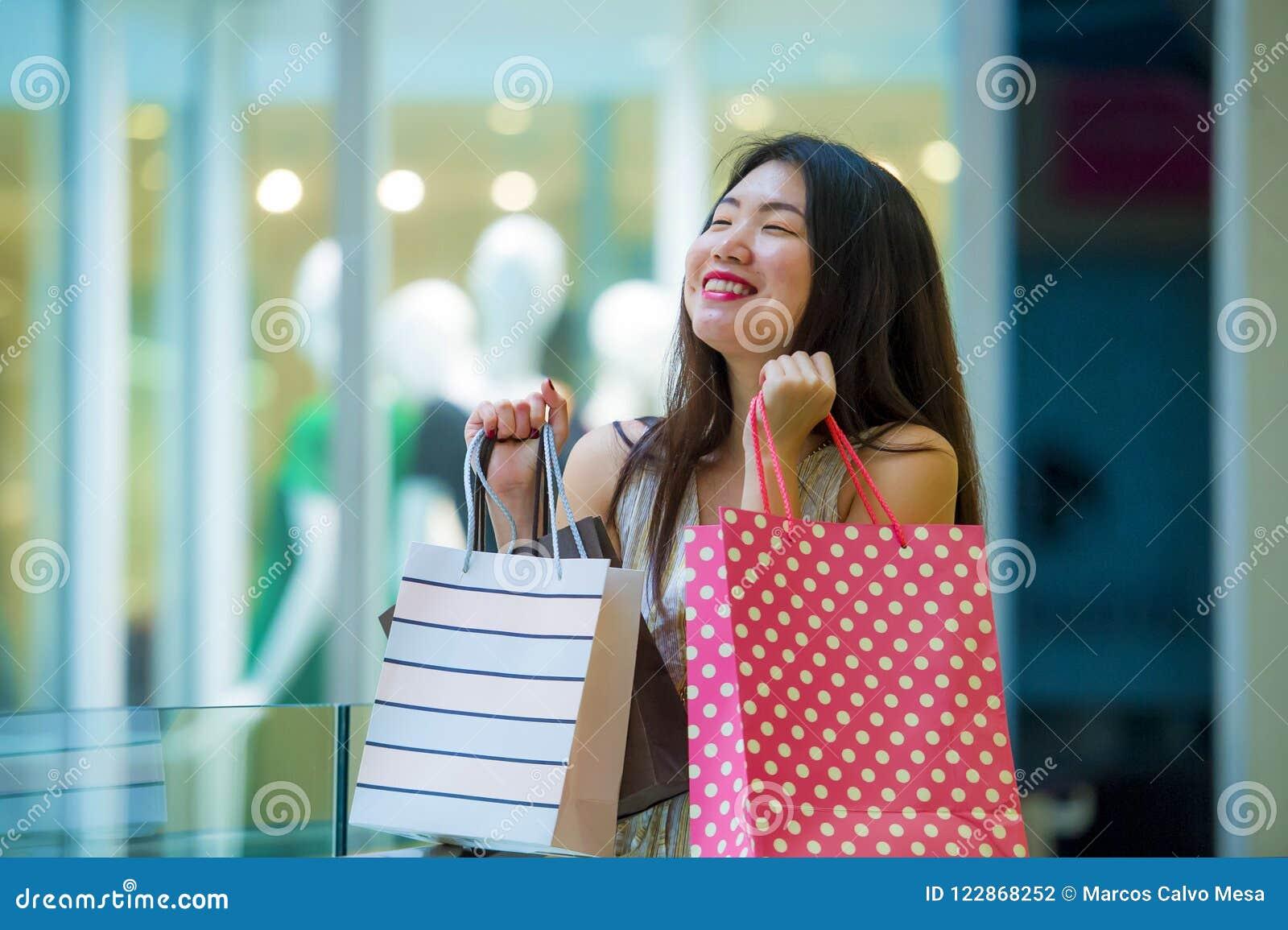 Образа жизни портрет внутри помещения молодых хозяйственных сумок нося счастливой и красивой азиатской корейской женщины в моле п