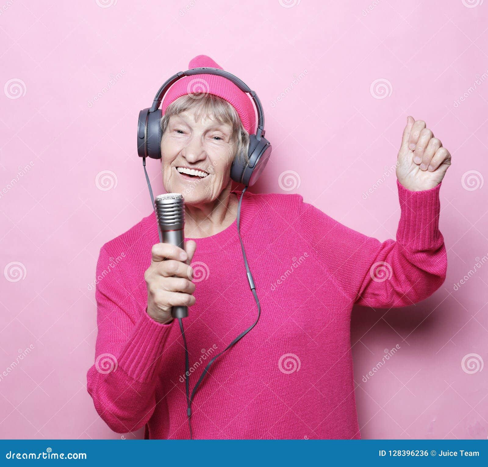 Образ жизни и концепция людей: Музыка смешной пожилой женщины слушая с наушниками и петь с mic