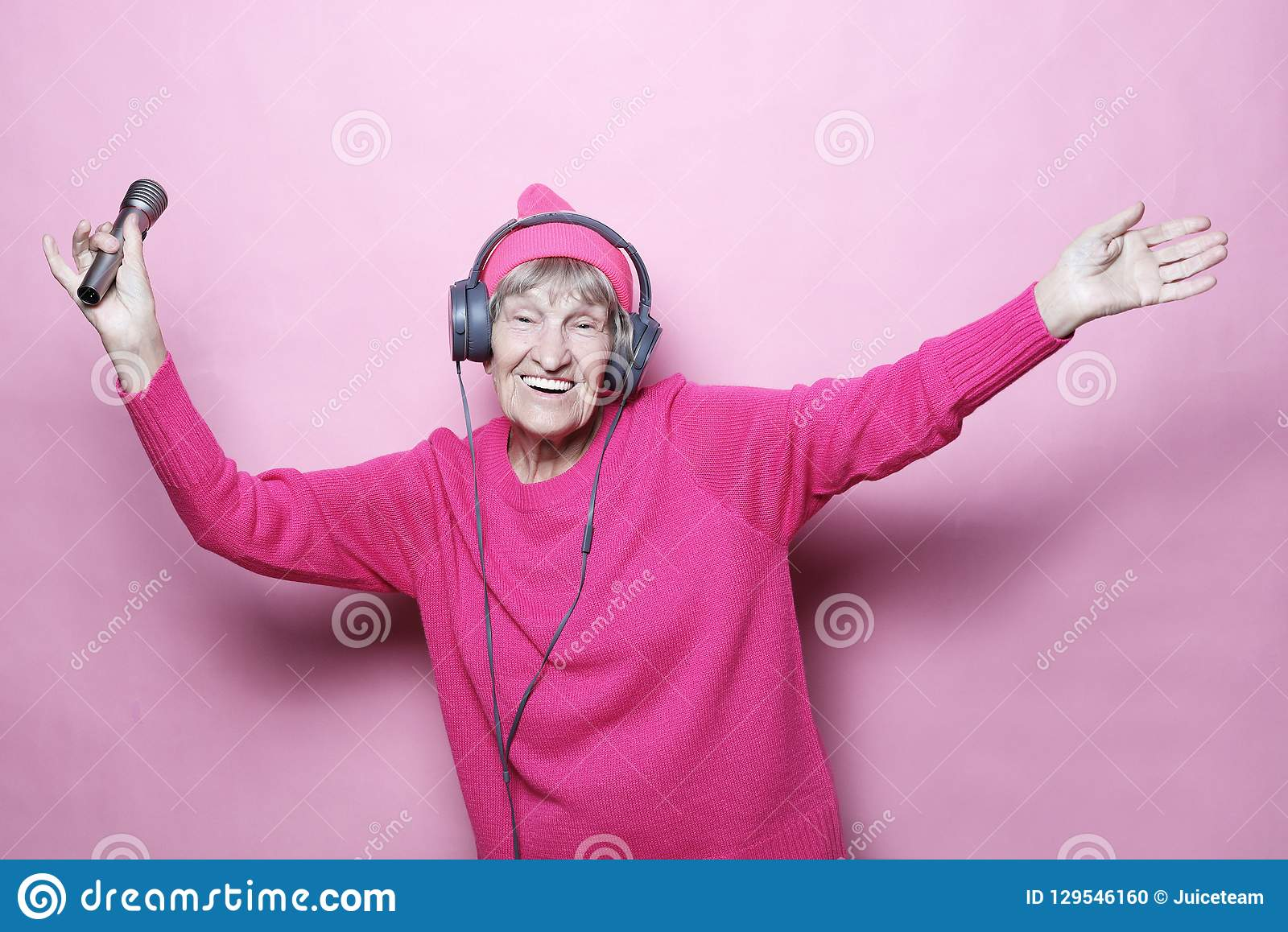 Образ жизни и концепция людей: Музыка смешной пожилой женщины слушая с наушниками и петь с mic над розовой предпосылкой