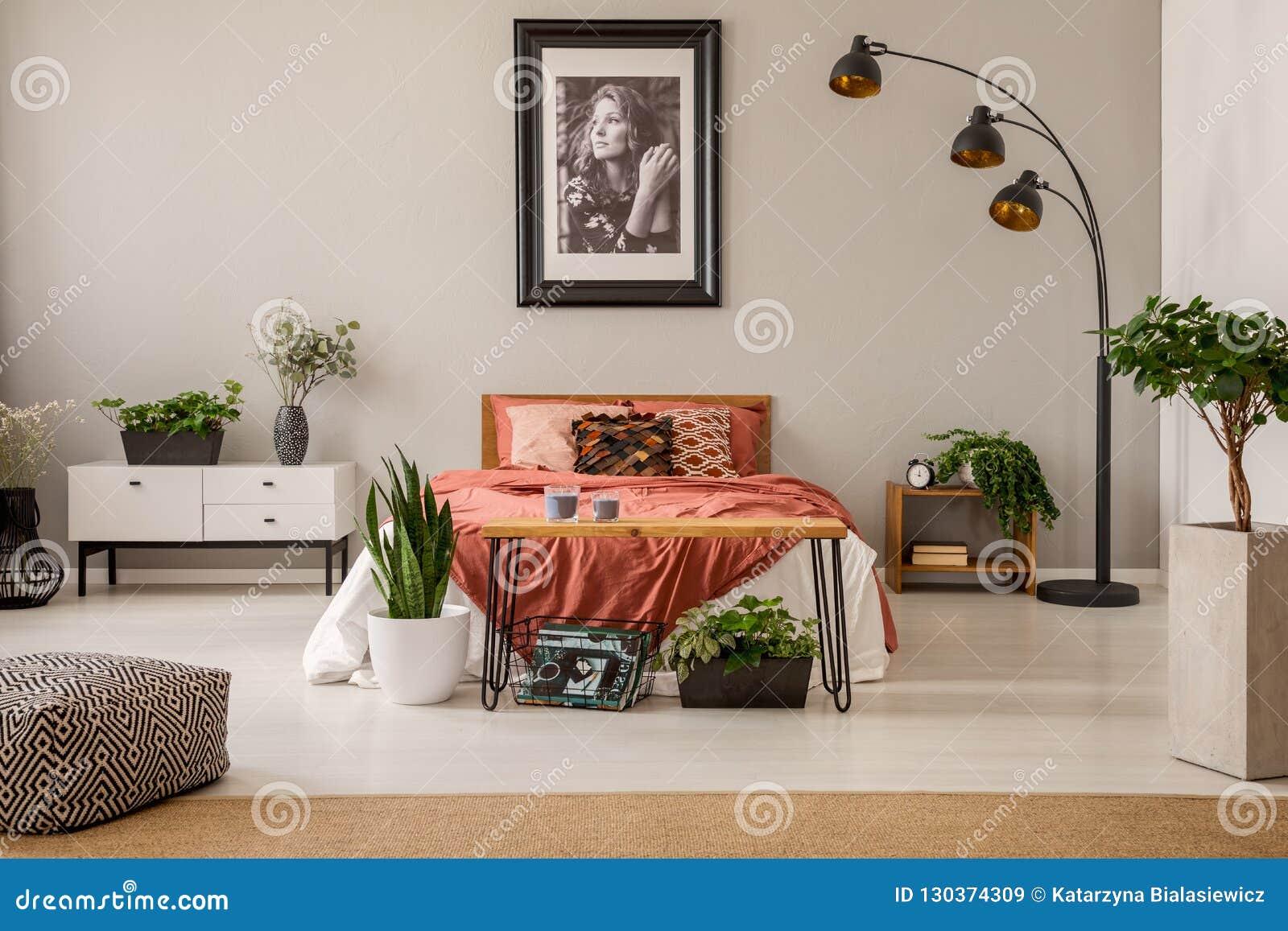 Обрамленный плакат красивой девушки над королевской кроватью с постельными принадлежностями цвета ржавчины в просторном интерьере