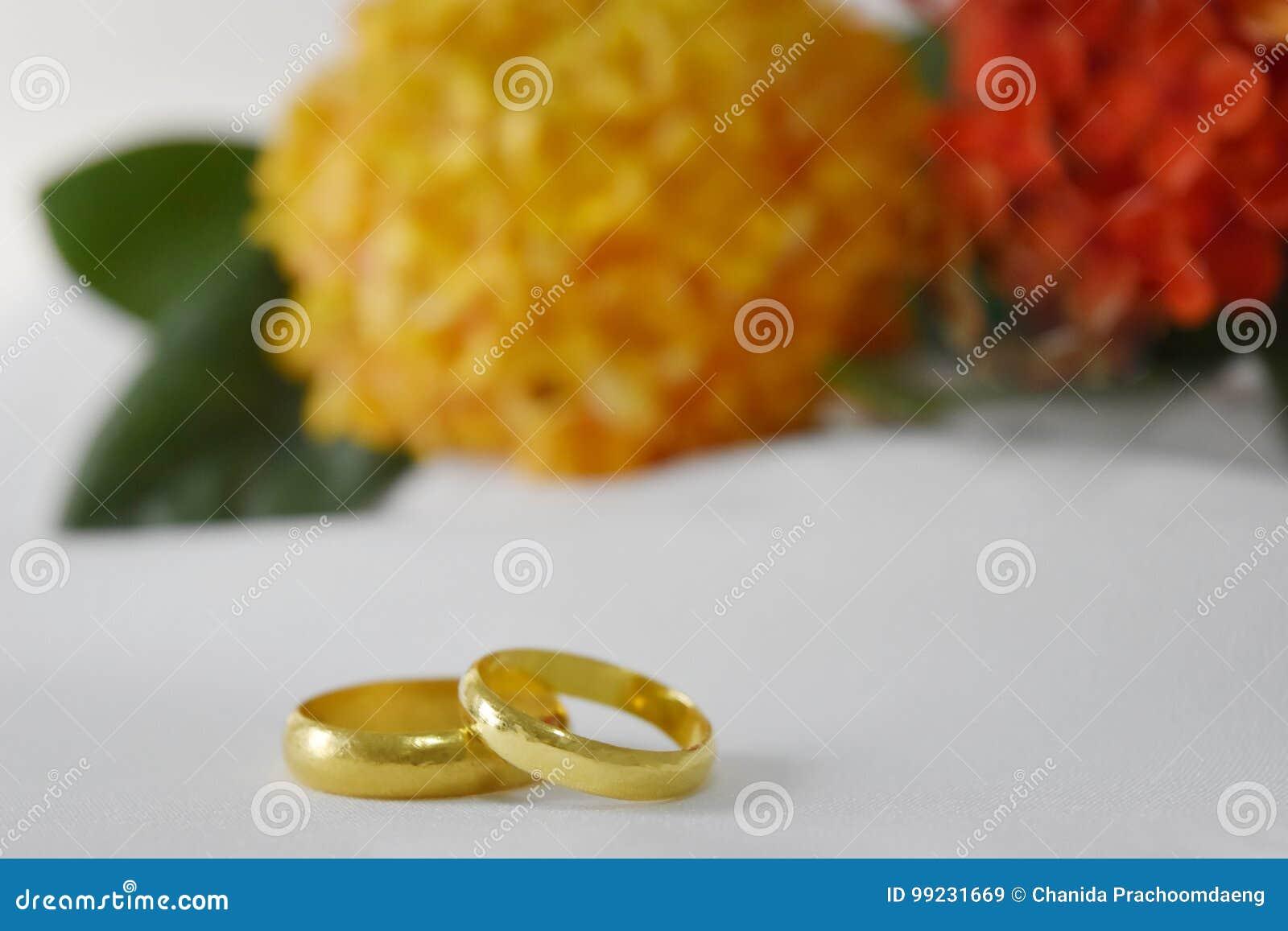 Обручальное кольцо золота имеет специальный день На заднем плане космос цветка нерезкости желтый и красный, пустой для текста