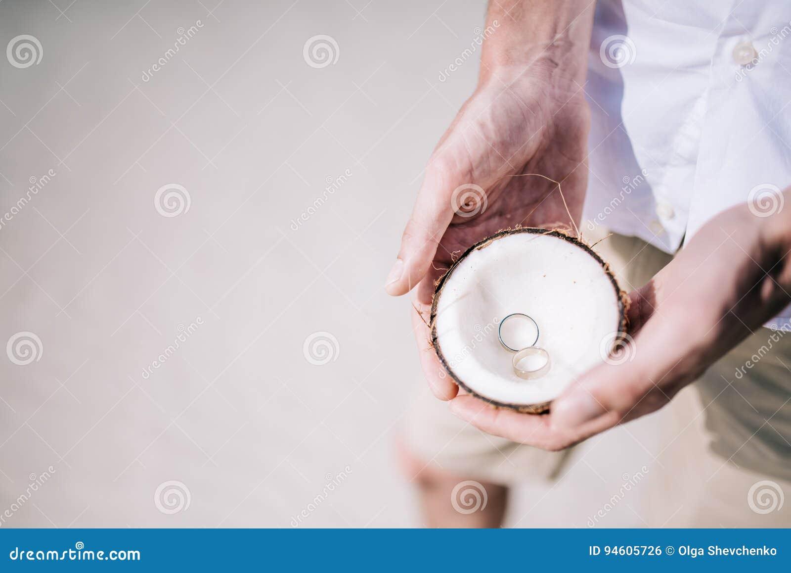 Обручальные кольца внутри кокоса на тропическом пляже