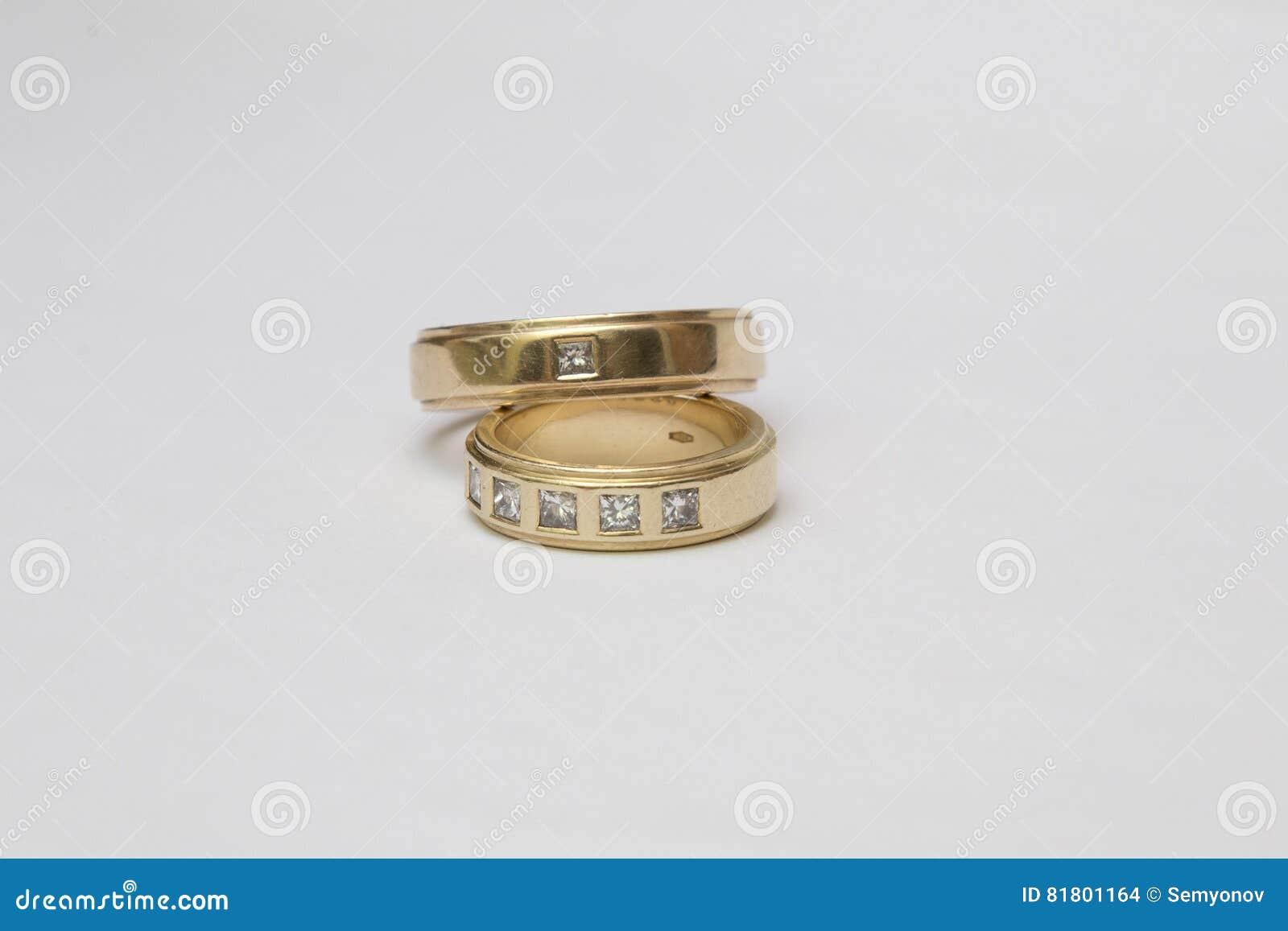 Обручальные кольца желтого золота при диаманты изолированные на белизне