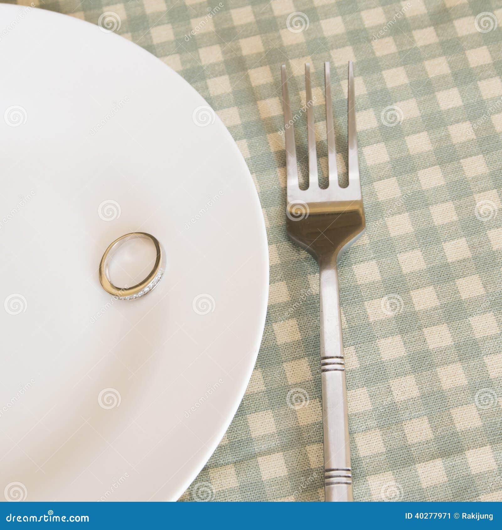 Обручальные кольца на плите с вилкой