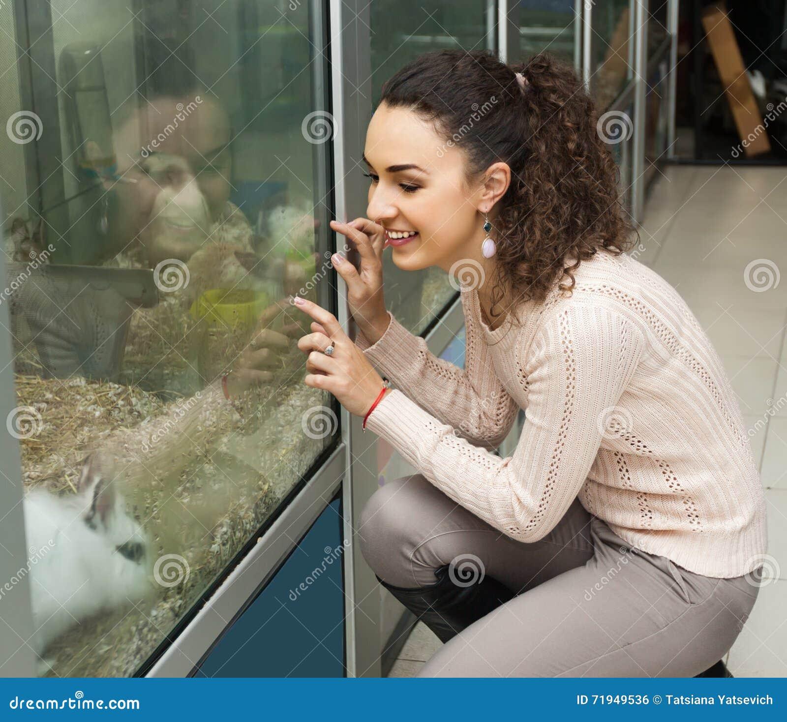 Обычный женский клиент наблюдая кролика Blanc de Hotot