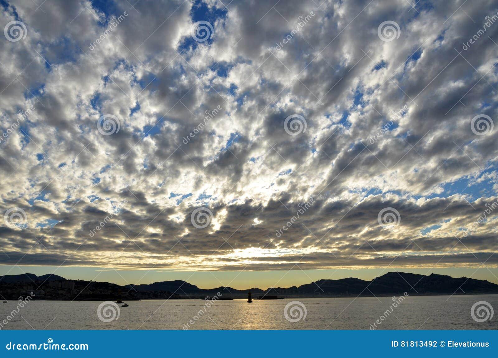 Облака над морскими водами на восходе солнца, марселями, Францией