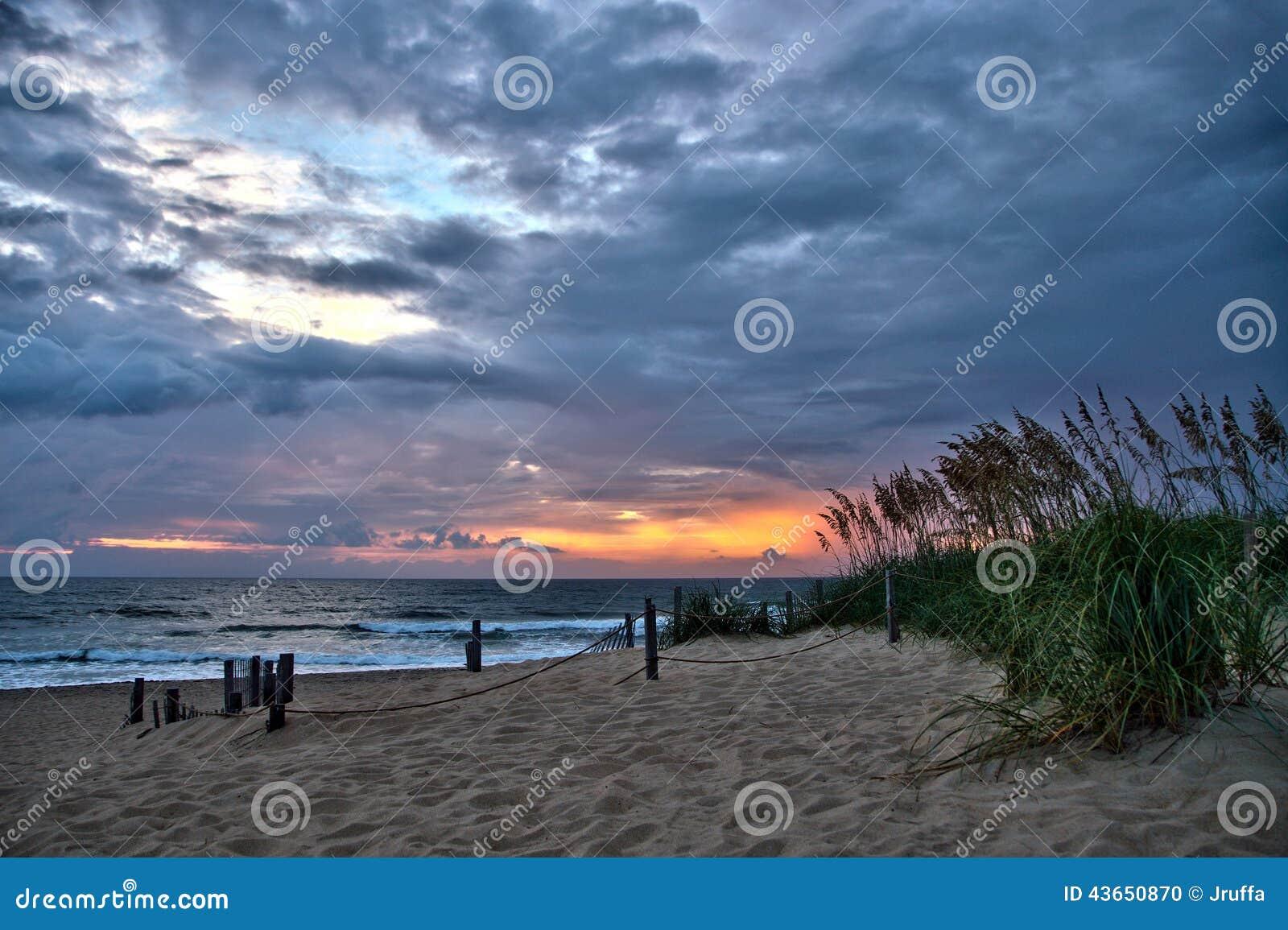 Облака шторма на восходе солнца пляжа