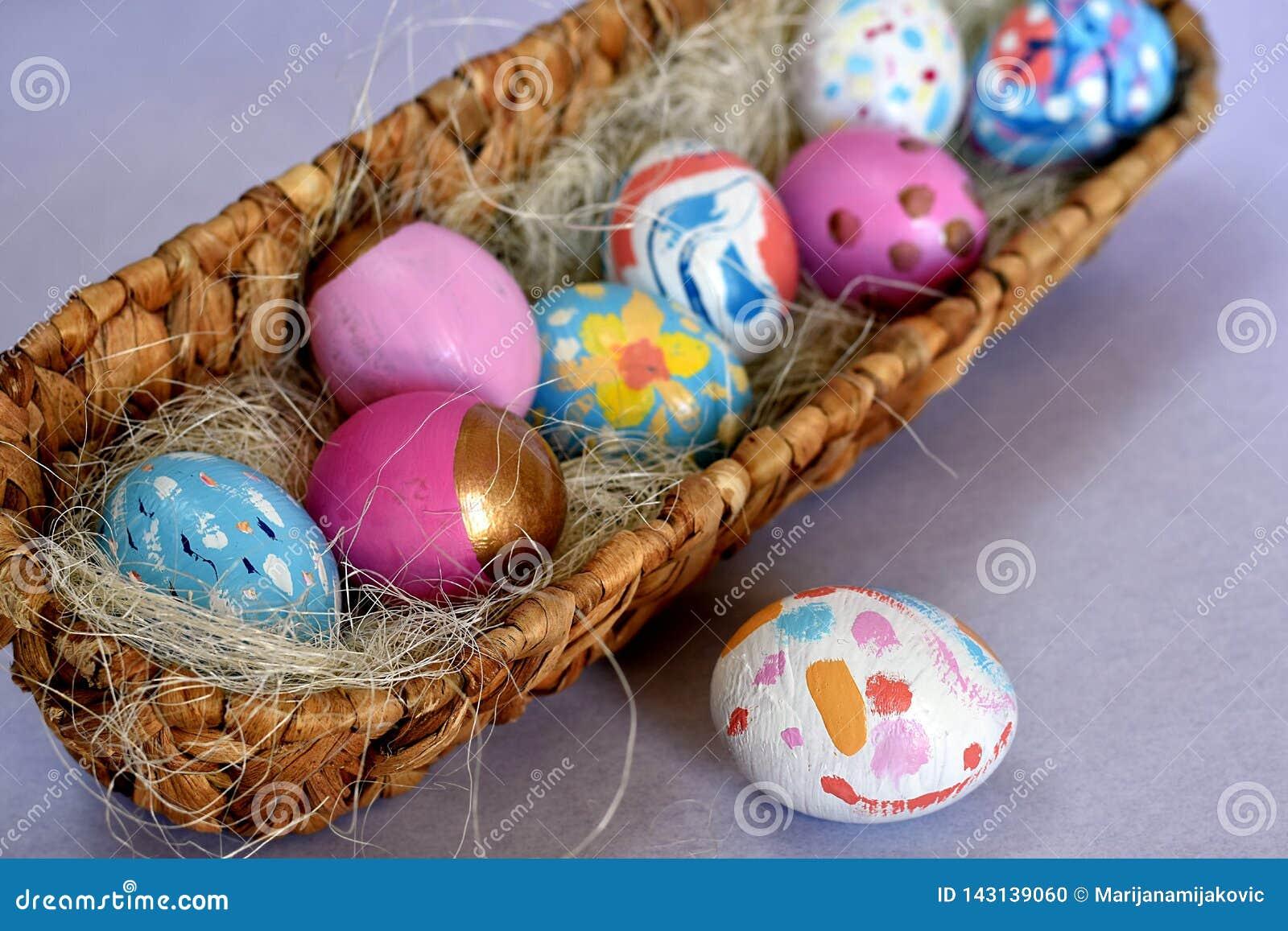 Овальная корзина вполне ярко покрашенных пасхальных яя с одним белым запятнанным яйцом рядом с