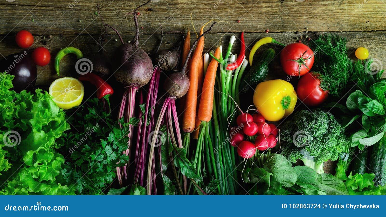 Овощи на деревянной предпосылке Био здоровые натуральные продукты, травы и специи Сырцовая и вегетарианская концепция ингридиенты