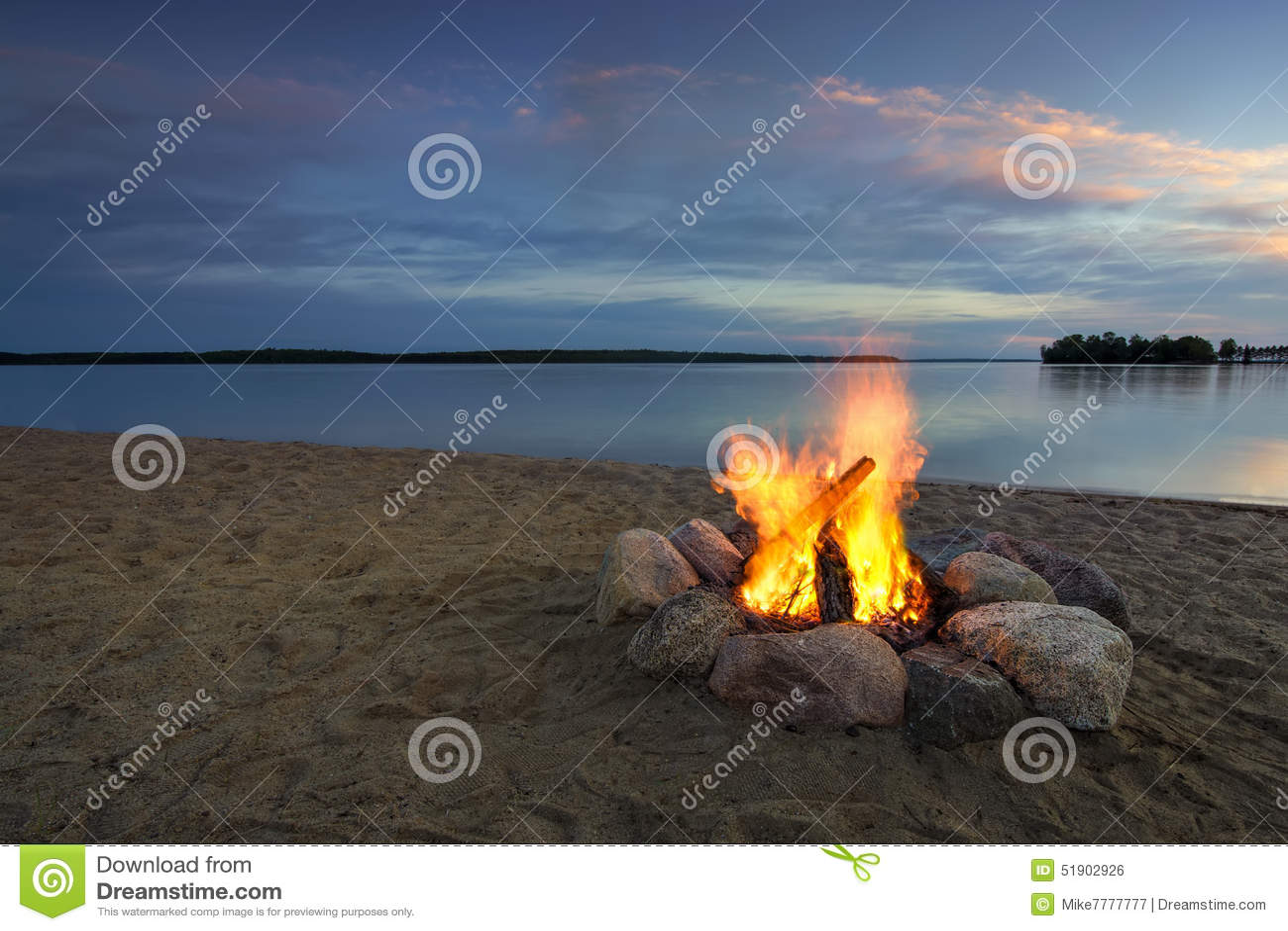 Огонь лагеря на песчаном пляже, около озера на заходе солнца Минесота, США