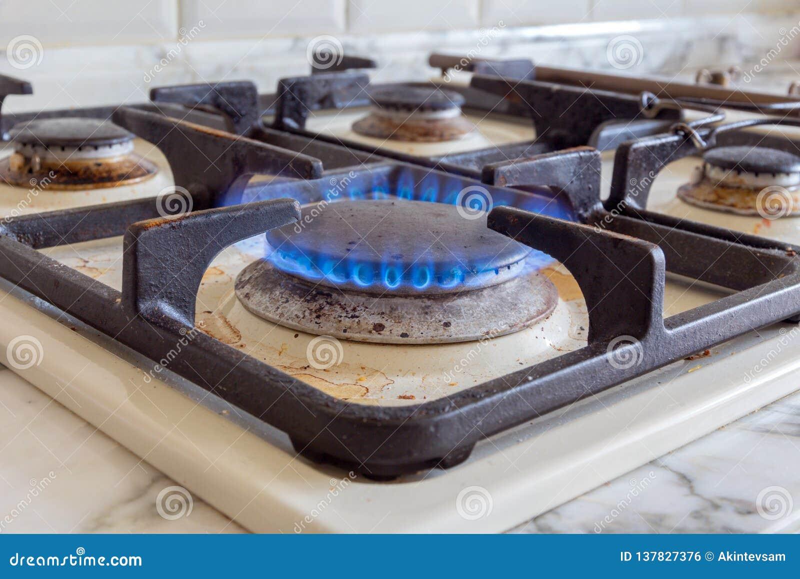 Огонь на грязной газовой плите кухни