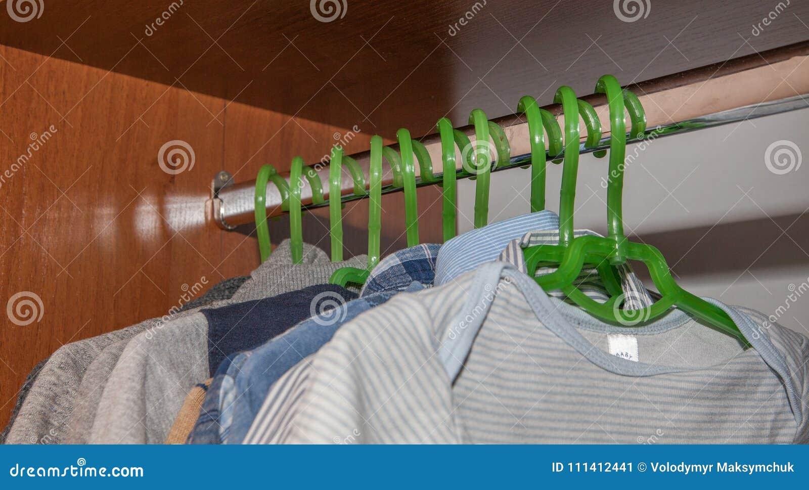 Одевать шкаф с комплементарными одеждами аранжировал на вешалках Красочный шкаф newborn, дети, младенцы вполне всех одежд, ботинк