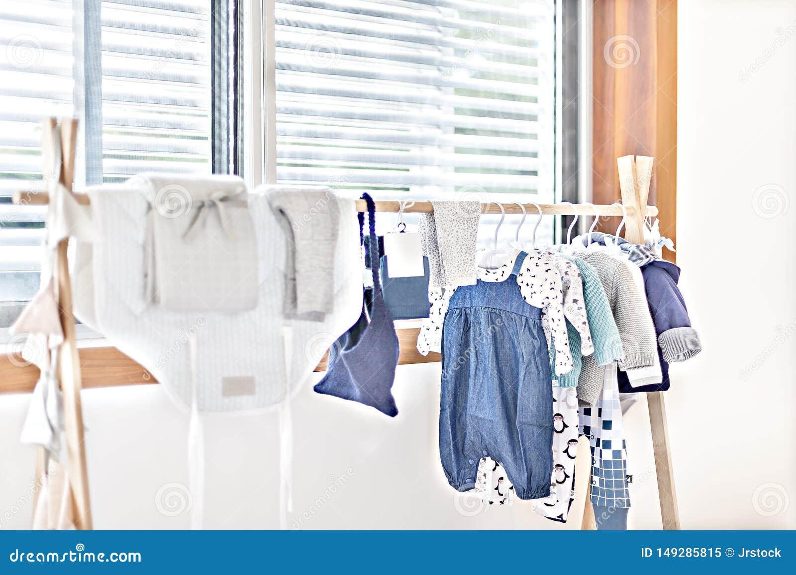 Одежда младенца или платья детей вися около окна