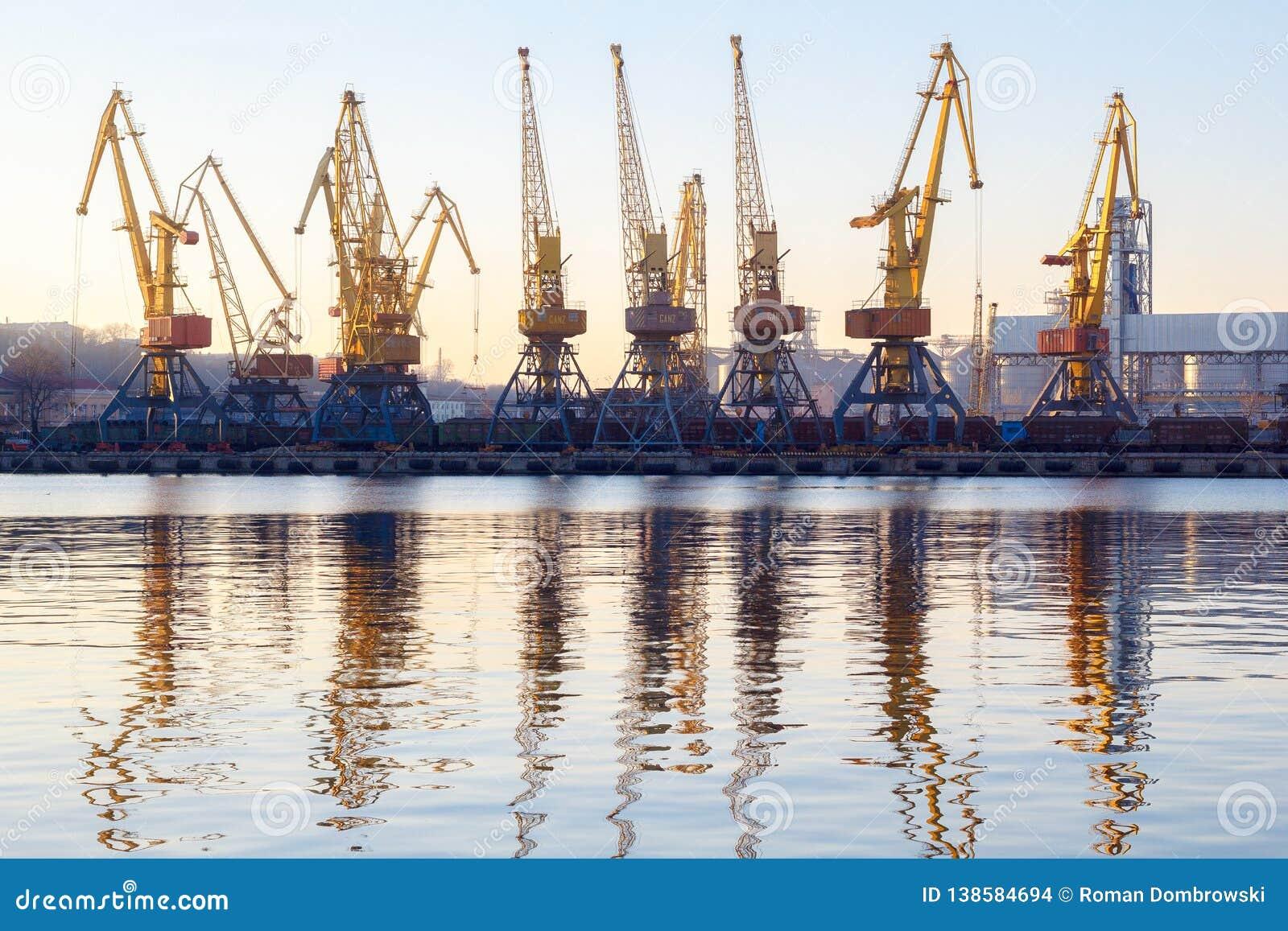 Одесса, Украина - Januadry 02, 2017: Краны в терминале порта груза, краны контейнера груза отразили в воде Заход солнца