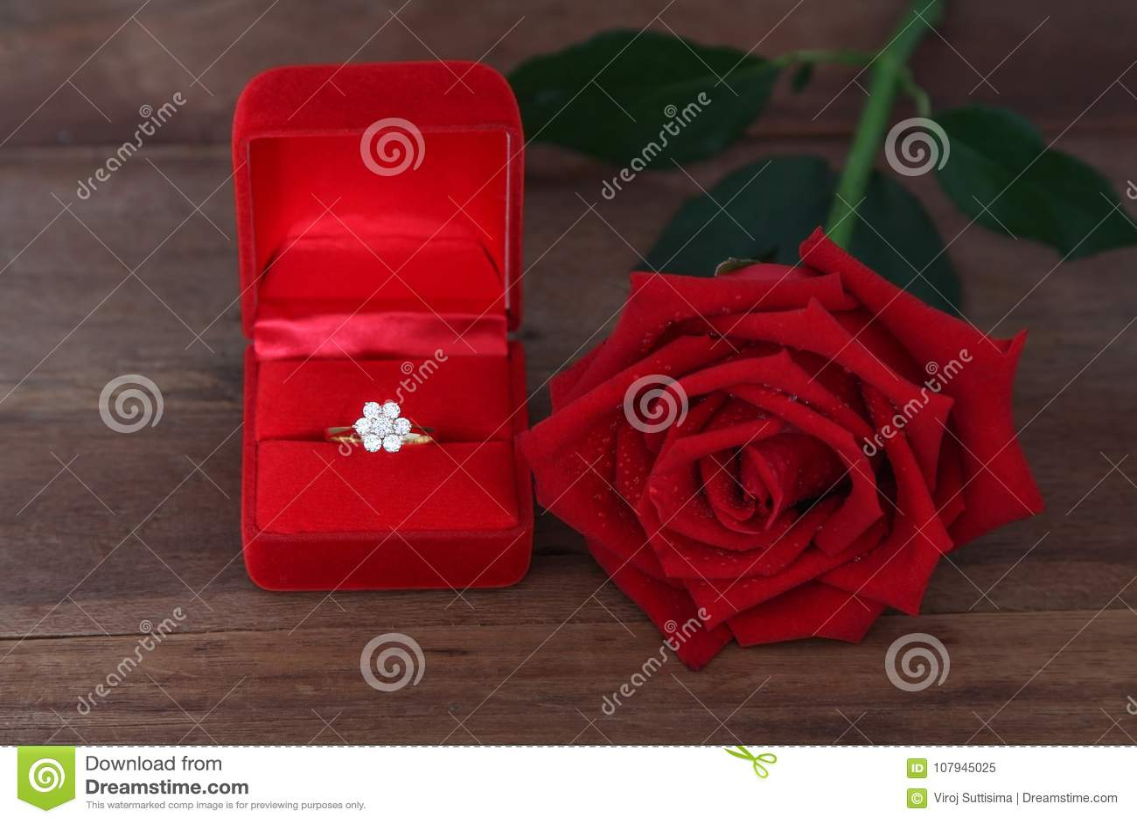 Одиночные красные розы и диаманта обручальное кольцо в красной коробке на деревянной предпосылке