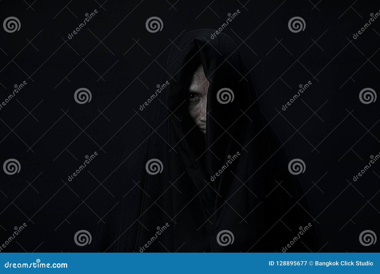 Один глаз человека в черной крышке смотря к камере на черном backgro