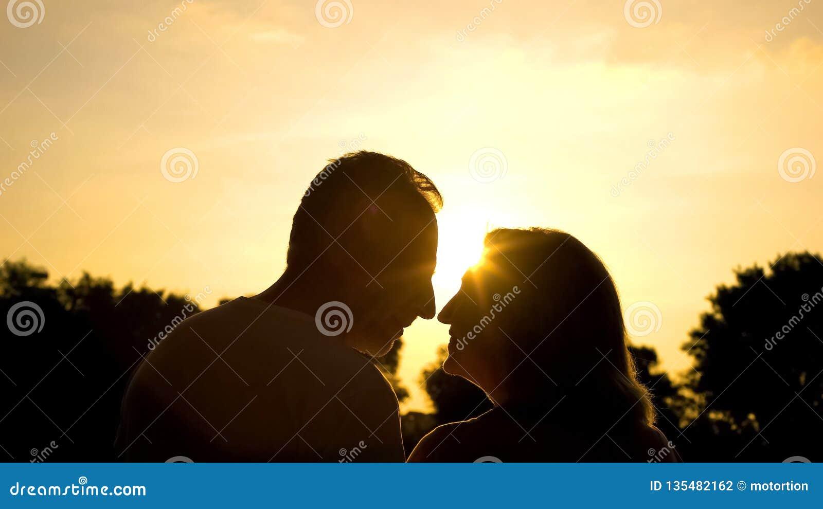 Один другого старшего человека и женщины усмехаясь, романтичная дата в парке на заходе солнца, любовь