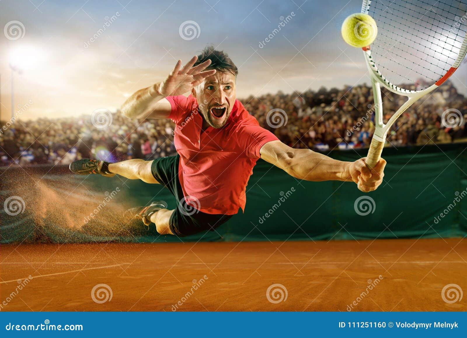 Один скача игрок, человек кавказца подходящий, играя теннис на землистом суде с зрителями