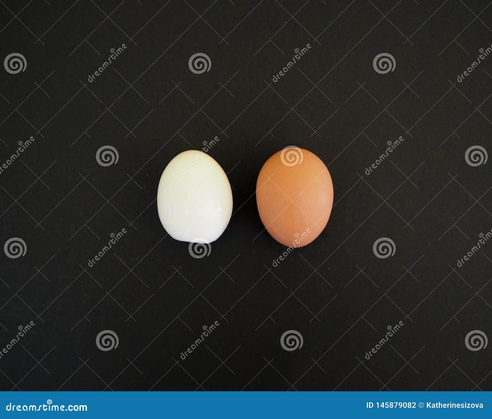 Одно целое яйцо и одно яйцо без eggshell на черноте