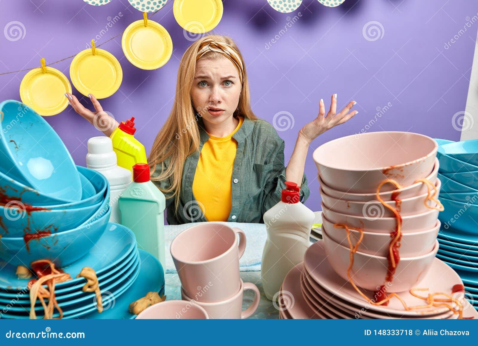 Озадаченная белокурая девушка в стильное случайном одевает сидеть за грязной кухней