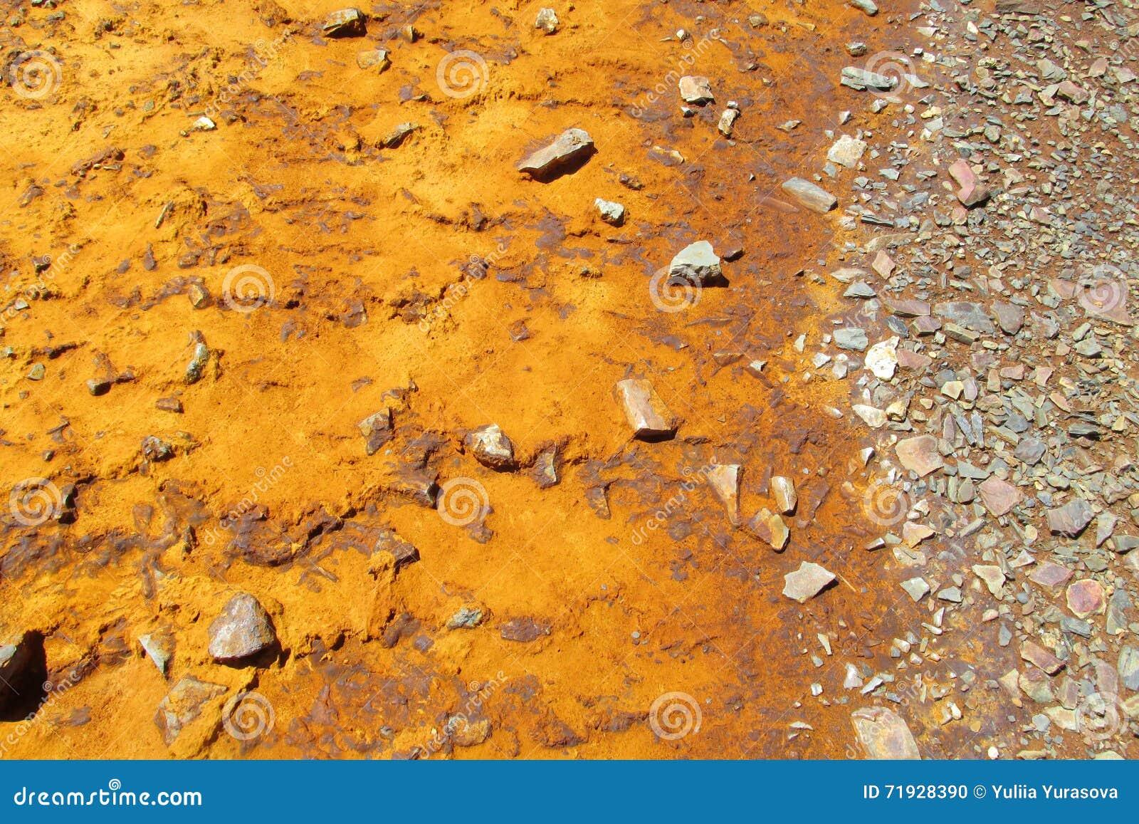 Озеро гор с оранжевой водой цвета металла