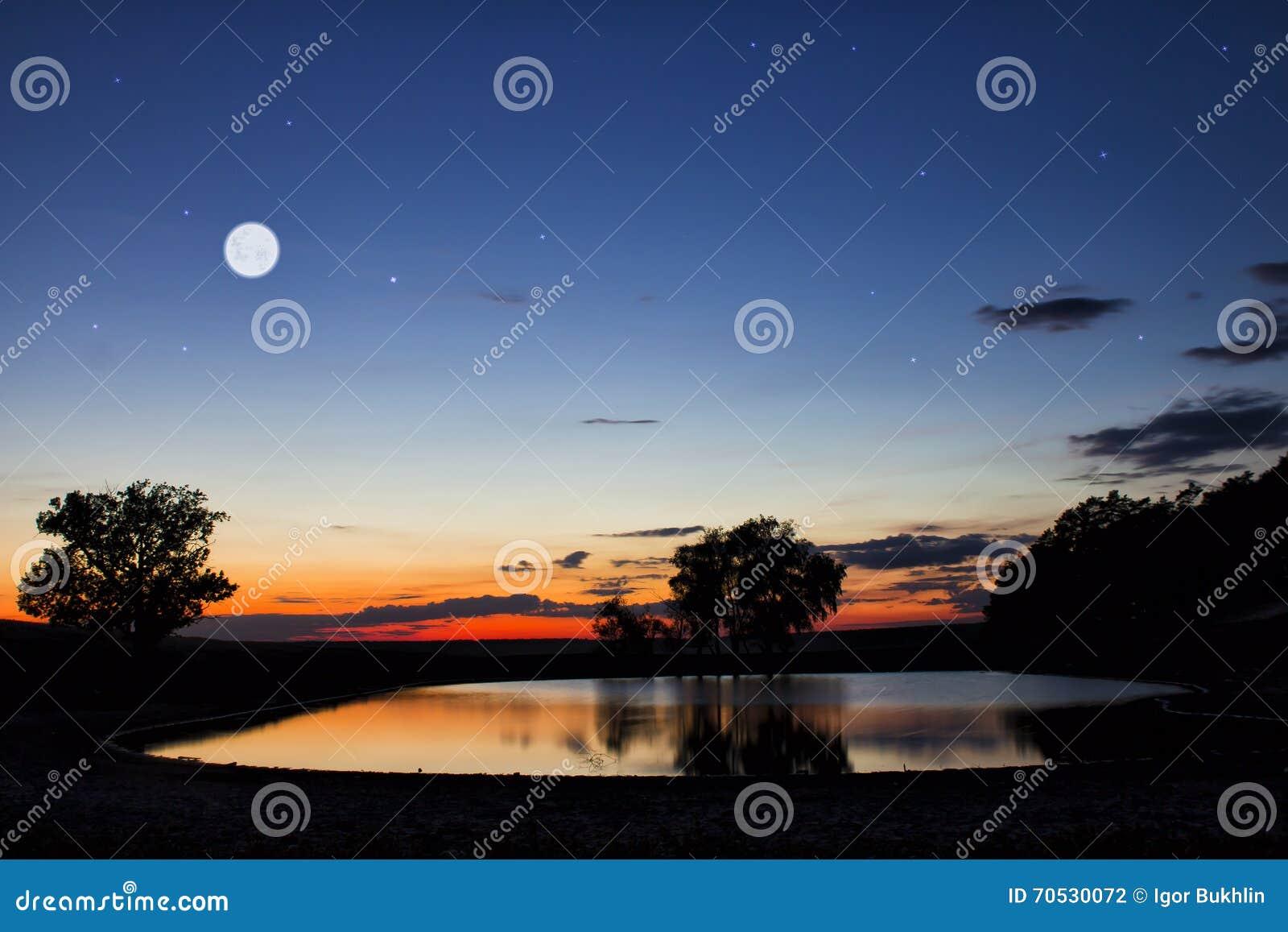 Озеро древесин в горах на заходе солнца
