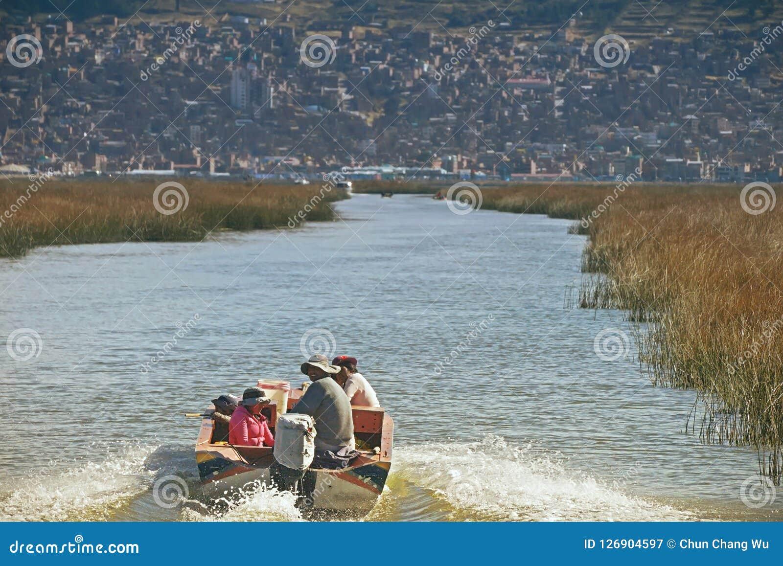 Озеро Titicaca, Перу - 17-ое августа 2018: Семья peruvian плавает на озере Titicaca, большом, глубоком озере в Андах на границе