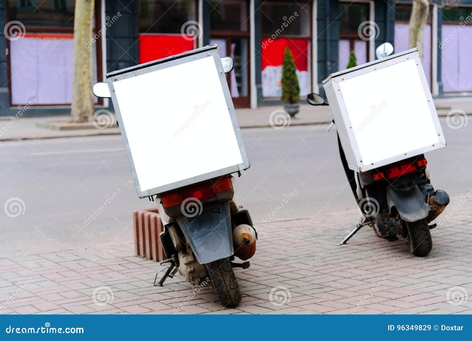 Оказание услуг доставки мопедов припарковало на обочине, вид сзади