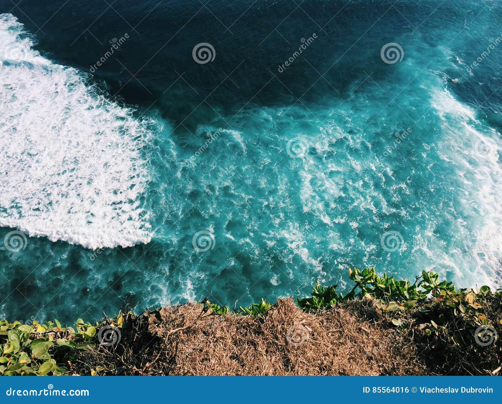 Океан и сулой завивают взгляд от скачком побережья скалы, ландшафт моря Бали