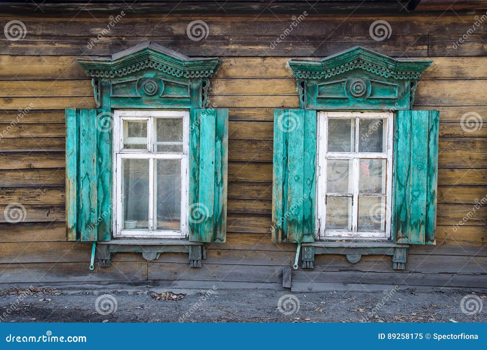 2 окна с деревянным высекаенным architrave в старом деревянном доме в старом русском городке
