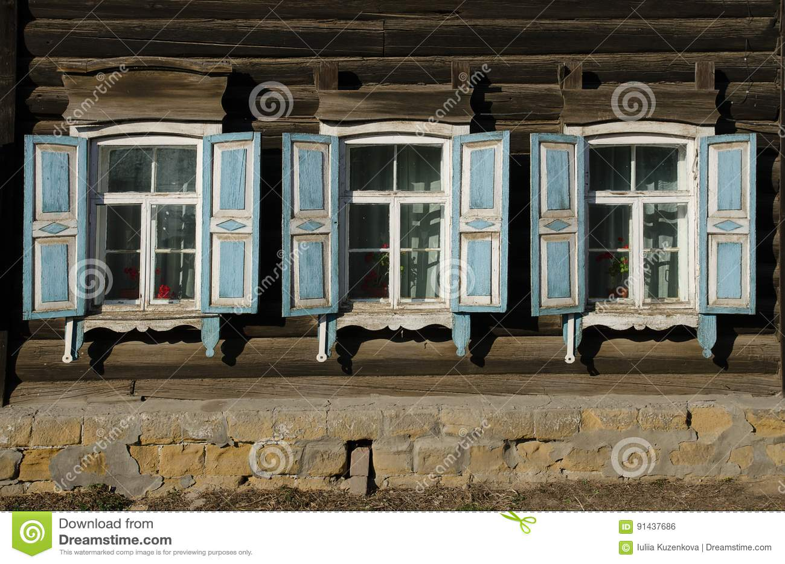 Окно с деревянным высекаенным architrave в старом деревянном доме в старом русском городке