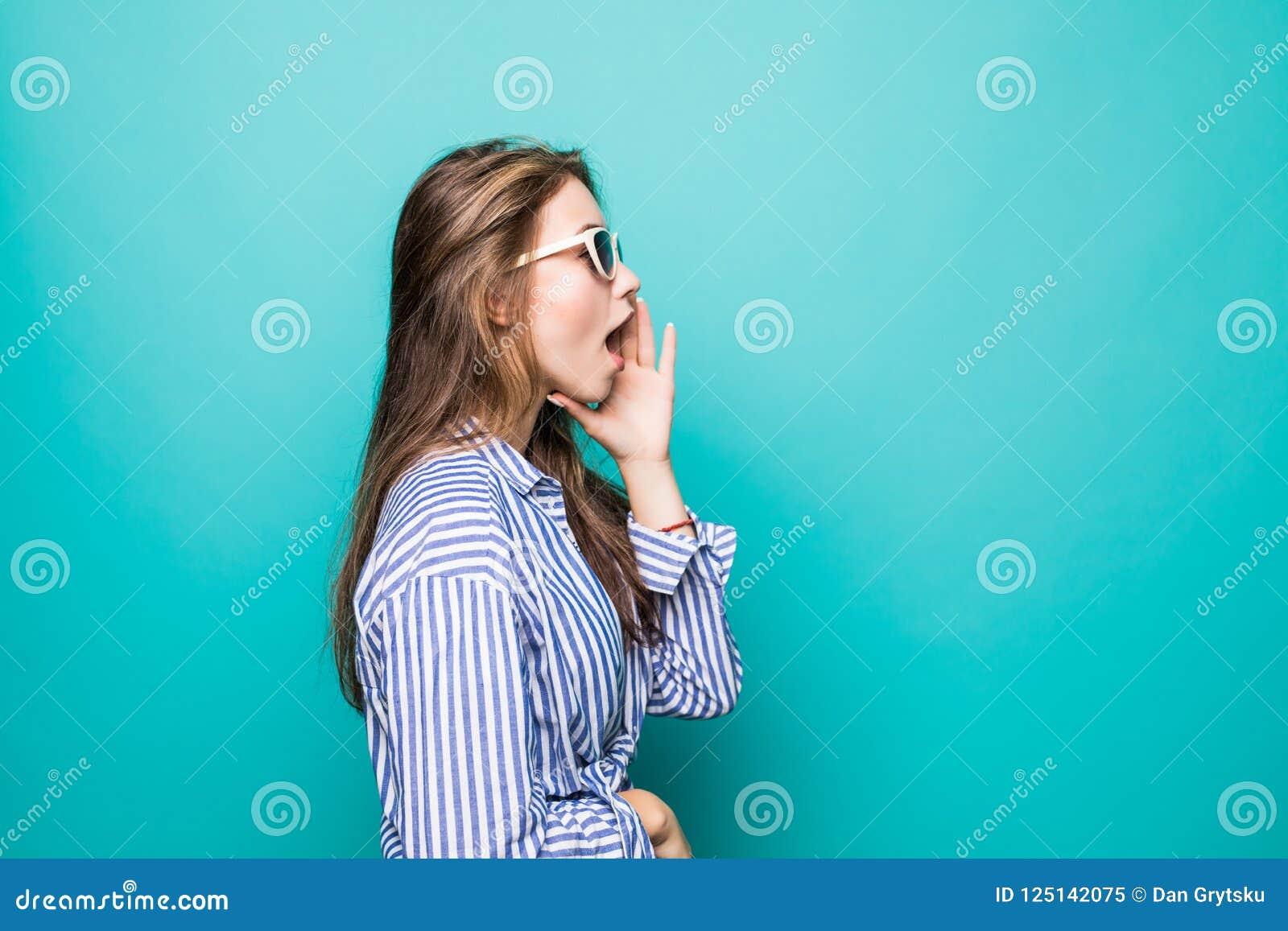 Окрика девушки t взгляда со стороны рот привлекательного милого открытые и руки удержания около губ пока стоящ на голубой предпос