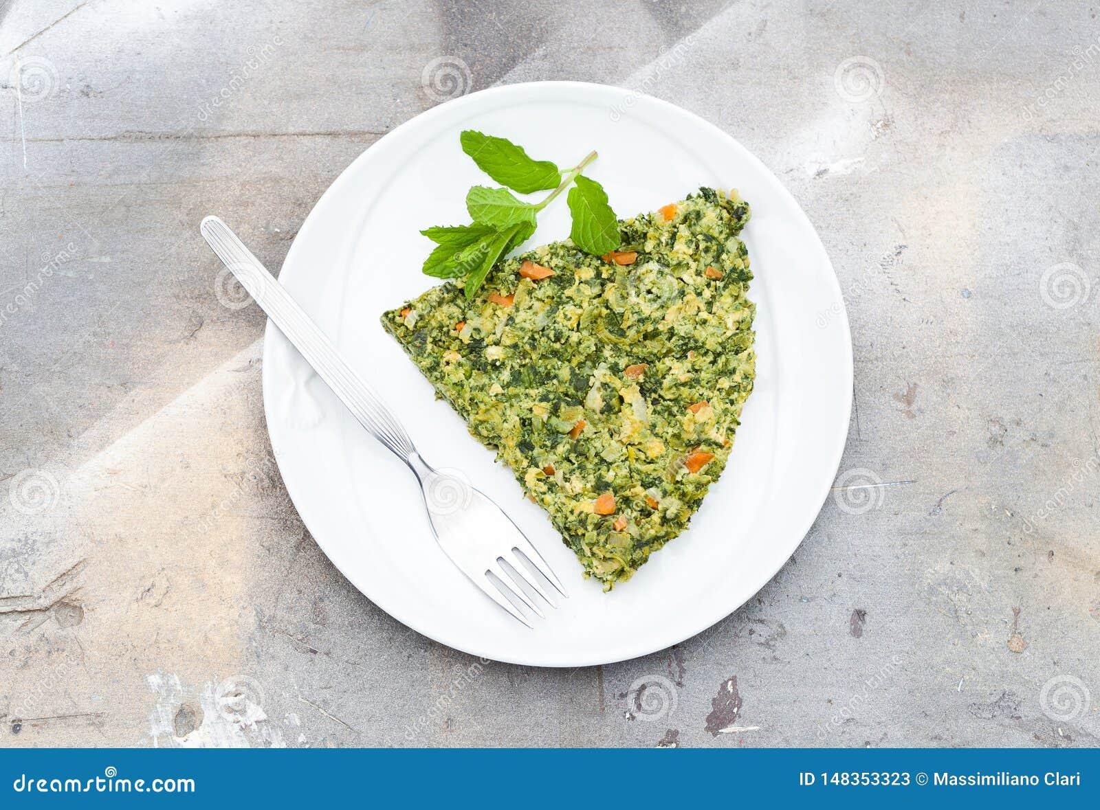 Омлет сделанный из яя, зеленой спаржи, гороха, моркови, сыра, петрушки и мяты, деревянной предпосылки с естественным светом
