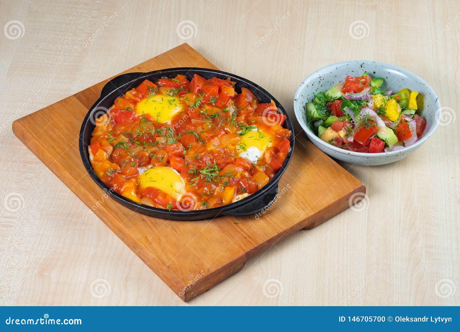 Омлет со сладкими перцами в griddle на деревянной салате доски и овоща