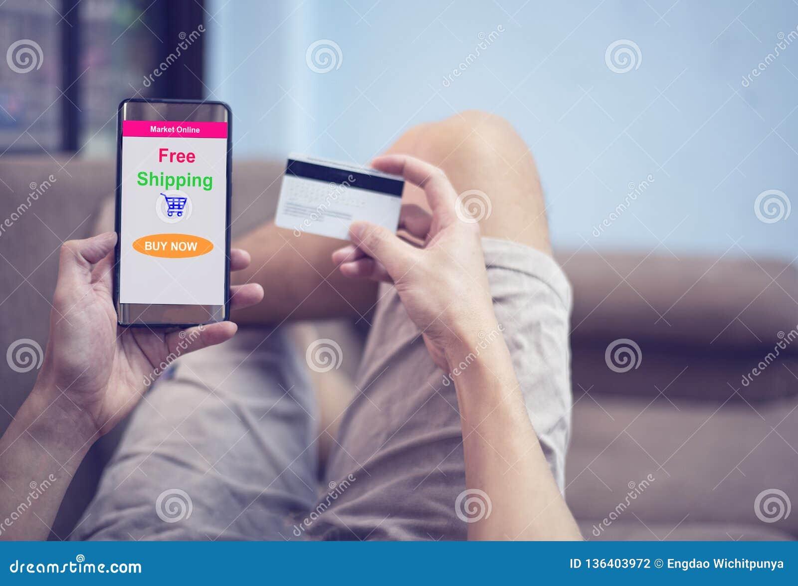Онлайн ходя по магазинам концепция - молодой человек используя покупки смартфона в рынке вебсайта онлайн и руки держа кредитную к