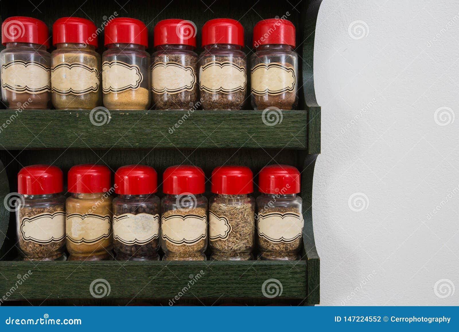 Опарникы трав и специй в деревянном шкафе на белой предпосылке, винтажном дизайне