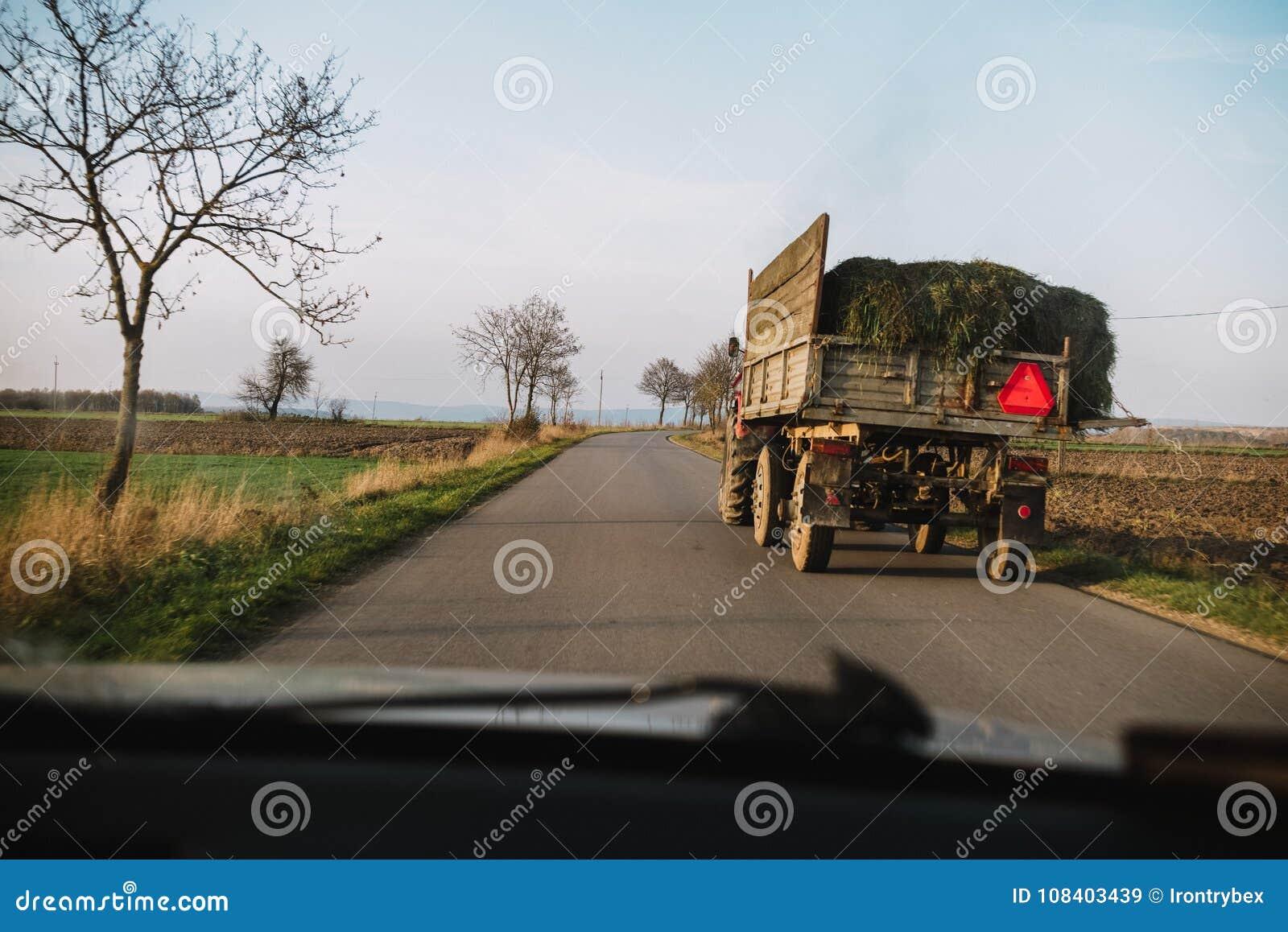 Опасность в дороге трактор с травой на улице, взглядом от